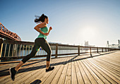 Caucasian woman jogging on urban waterfront