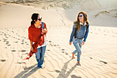 Mixed race women walking on sand dunes