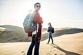 Mixed race women standing on sand dunes