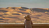 Caucasian woman admiring sand dunes in desert landscape