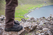 Person standing on a rock in the mountains in the near of a village at the sea, Faeroe Islands