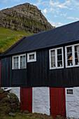 Altes Haus in der Nähe eines grün bewachsenen Berges, Färöer Inseln