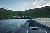 Blick von einem Boot auf ein kleines Dorf an einem grün bewachsenen Berg, Färöer Inseln