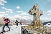 A group of skiers walking past a stone cross in the mountains, Gudauri, Mtskheta-Mtianeti, Georgia