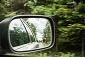 Blick in den Auto Außenspiegel auf eine Landstraße mit einem roten Holzhaus, Halland, Schweden