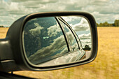 view into the car wing mirror, summer landscape, field, clouds, Smaland, Sweden