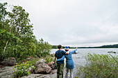 couple standing on the shore and looking across lake vanern, Smaland, Sweden