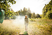 Kind nach der morgendlichen Dusche auf einer Wiese im Sonnenlicht, Halland, Sweden