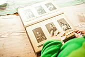 Kind blickt in ein Fotoalbum mit Fotografien aus alten Zeiten im Heimatmuseum Gammelgarden in Rättvik, Dalarna, Schweden