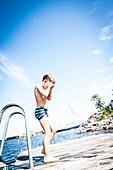 Junge steht nach dem Bad im Meer auf dem Bootssteg, Anskarsklubb, Öregrund, Uppsala, Schweden