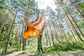 Mann schüttelt am Morgen sein Zelt aus im Wald von Trollegater, Kinda, Östergötland, Schweden