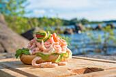 Brötchen mit Krabben, Ei, Gurke und Zitrone auf einem Holzbrett im Sommer am Vänern See, Smaland, Schweden