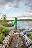 child standing on a rotten fishing boat on the shore of a small lake near Munkfors, Varmland, Sweden