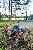 Blue enamel kettle standing on a grate on a camp fire near a small lake, Varmland, Sweden