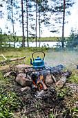 Blauer Wasserkessel aus Emaille steht auf einem Rost über dem Lagerfeuer am See, Värmland, Schweden