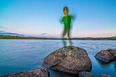 laughing child standing on a rock at dusk at a lake near Munkfors, Varmland, Sweden