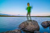 lachendes Kind steht auf einem Stein im See im Abendlicht wie ein Schemen, See nähe Munkfors, Värmland, Schweden