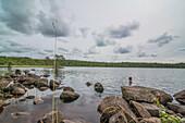 Mann badet an einem kühlen Sommertag im See, Värmland, Schweden