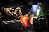 Großaufnahme von Händen, die eine Axt schmieden in der Axtschmiede Wetterlings, Storvik, Gävleborg Iän, Schweden