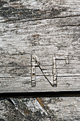 Close up of the letter N on a weathered plank, Oregrund, Uppsala, Sweden