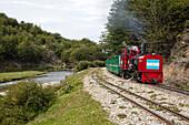 'Ferrocarril Austral Fueguino ''End of the World'' gauge steam train for tourist sightseeing alongside Rio Pico river near Ushuaia, Tierra del Fuego, Patagonia, Argentina'