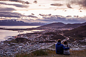 Couple overlook city from Arakur Ushuaia Resort and Spa at sunset Ushuaia, Tierra del Fuego, Patagonia, Argentina