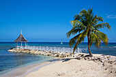 Sunset Beach and jetty with pavilion at Half Moon Resort with Hobie Cat sailboat in Caribbean Sea Rose Hall, near Montego Bay, Saint James, Jamaica