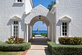 Entrance to villa at Royal Court of Half Moon Resort with Hobie Cat sailboat in Caribbean Sea behind Rose Hall, near Montego Bay, Saint James, Jamaica
