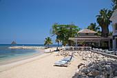 Beach chairs on Sunset Beach, Cedar Bar and jetty with pavillion at Half Moon Resort Rose Hall, near Montego Bay, Saint James, Jamaica