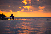 Silhouette of people in shallow water and pavillion on jetty at sunset Rose Hall, near Montego Bay, Saint James, Jamaica