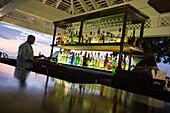 Barkeeper at Cedar Bar of Half Moon Resort at dusk Rose Hall, near Montego Bay, Saint James, Jamaica