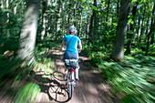 Fahrradfahren im Wald, Bewegung, verwischt, Fahrradtour, Freizeit, Mecklenburg-Vorpommern, Deutschland