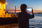tourist with Tablet photographs sunset on riverfront, restaurant Ponto Final, view from south bank of River Tagus,and the 25th April Bridge, Cacilhas, Almada, Lisbon, Portugal