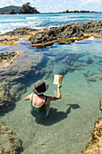 person relaxing, reading in rockpool, Elliot Bay, North Island, New Zealand