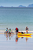 kids with bikes, adults with yellow kayaks, typical summer holiday beach, ocean, North Island, New Zealand