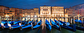 Panorama overlooking the Grand Canal with the illuminated facades of Palazzo Ca 'Loredan and Palazzo Ca' Farsetti (from left) in blue night and gondolas in the foreground, San Marco, Venice, Veneto, Italy