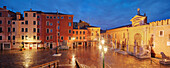 Panorama of Campo de L'Arsenal with the illuminated facade of the arsenal, the former shipyard and naval base in the blue of the night, Portal Ingresso di Terra right, Castello, Venice, Veneto, Italy