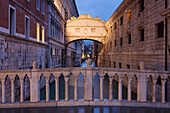 View from the Ponte della Paglia to Bridge of Sighs with the canal Rio del Palazzo in blue at night, San Marco, Venice, Veneto, Italy