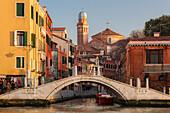 Overlooking the Grand Canal on houses and the Church of San Nicola da Tolentino at the canal Rio dei Tolentini with bridge in the setting sun, Santa Croce, Venice, Veneto, Italy