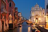 View of the canal Rio dei Mendicanti with illuminated Scuola Grande di San Marco, the historic facade of the Ospedale hospital and boats in the blue night, Sestiere Castello, Venice, Veneto, Italy