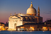 Overlooking the lagoon of Venice on the Giudecca island with the illuminated church Il Redentore in blue at dawn, Venice, Veneto, Italy