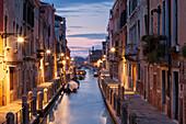 Illuminated Houses at Rio de la Fornace with boats in the blue dawn, Dorsoduro, Venice, Veneto, Italy