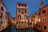 Illuminated house between channels Rio di San Giovanni Laterano and Rio de la Tetta in blue twilight, Castello, Venice, Veneto, Italy