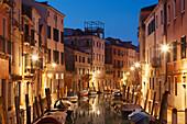 Illuminated facades and boats on the canal Rio Ognissanti in blue night, Dorsoduro, Venice, Veneto, Italy