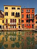 Bunte Häuser mit Spiegelung im Kanal Rio di Santa Fosca in der Morgensonne und blauem Himmel, Cannaregio, Venedig, Venezien, Italien