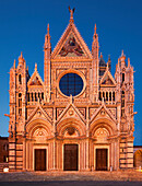 Facade of the cathedral Cattedrale di Santa Maria Assunta in Siena with the Porte, round glass windows and frescoes in the blue hour, Tuscany, Italy