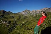Woman relaxing in summertime in green alpine area, Navis, Tyrol, Austria
