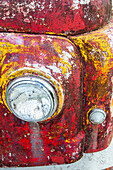 detail headlight of rusting old car, abandoned, red, yellow paint, South Island, New Zealand