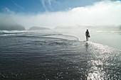 Wharariki Strand, Person mit Sandalen in der Hand, läuft durch das flache Wasser, Seenebel, Küstennebel, morgens, weiter Sandstrand, Natur, Landschaft, mystisch, Natur, Meer, Wasser, Westküste, Südinsel, Neuseeland