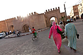 Couple approaching old city wall and ramparts, Taroudant, Morocco